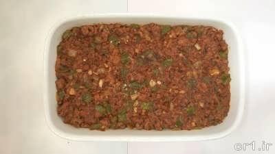 ریختن مایع گوشتی روی لایه بادمجان ها