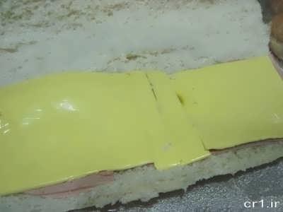 قرار دادن پنیر گودا و پنیر پیتزا روی لایه کالباس