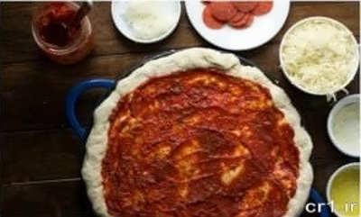 آغشته کردن خمیر پیتزا با سس